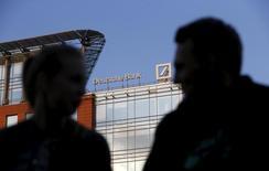 """Люди перед зданием, в котором расположен центральный офис Deutsche Bank в Москве. 14 сентября 2015 года. Российские клиенты Deutsche Bank могли использовать немецкий банк для """"отмывания"""" средств в гораздо больших объемах, чем ранее предполагалось, сказал Рейтер источник, знакомый с ситуацией. REUTERS/Sergei Karpukhin"""