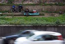 A man reads his book beside a highly trafficked street in central Rome in this April 11, 2015 file photo. REUTERS/Alessandro Bianchi/Files