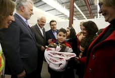 A Syrian refugee family is greeted by Quebec Premier Philippe Couillard (2nd L), Canada's Immigration Minister John McCallum (3rd L) and Montreal Mayor Denis Coderre (C) at the Welcome Centre in Montreal, Quebec, December 12, 2015.  REUTERS/Christinne Muschi