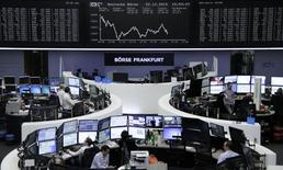 Las acciones europeas subieron con fuerza el miércoles, impulsadas por los avances en los valores relacionados con las materias primas por la subida de los precios de los metales y del petróleo. En la imagen, varios operadores financieros trabajan en sus mesas ubicadas dentro de la Bolsa de Fránkfort, delante del índice DAX, el 22 de diciembre de 2015. REUTERS/Staff/Remote