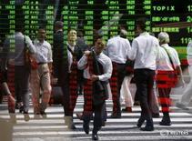 Peatones se reflejan en una panel que muestra la información de las acciones, en Tokio, Japón, 29 de septiembre de 2015. Un índice de acciones de Asia anotó el jueves un máximo en dos semanas y media, impulsado por las ganancias en Wall Street y una recuperación en los precios del crudo en medio de un débil volumen de negocios antes de Navidad. REUTERS/Issei Kato
