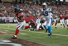 Dec 27, 2015; Atlanta, GA, USA; Atlanta Falcons running back Devonta Freeman (24) scores a touchdown past Carolina Panthers defensive end Jared Allen (69) in the second quarter at the Georgia Dome. Mandatory Credit: Jason Getz-USA TODAY Sports