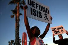 """Люди протестуют против ИГИЛ у мемориала жертвам перестрелки в Сан-Бернардино.  """"Исламское государство"""" сформировало министерства, занимающиеся """"военными трофеями"""", включая рабов, и разработкой месторождений природных ресурсов, например, нефтяных, создав внешние атрибуты правительства, позволяющие группировке управлять крупными территориями в Сирии, Ираке и других районах.REUTERS/Patrick T. Fallon"""