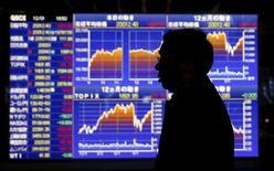 Un hombre camina delante de un tablero electrónico que muestra el movimiento reciente del índice Nikkei de Japón, afuera de una correduría en Tokio, Japón, 1 de diciembre de 2015. Las acciones japonesas avanzaron el lunes en una sesión con un volumen contenido de transacciones debido a que un repunte en los precios globales del crudo ayudaron a contrarrestar cifras decepcionantes de producción industrial y ventas minoristas de noviembre. REUTERS/Toru Hanai