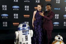 """Los miembros del reparto de """"Star Wars: El Despertar de la Fuerza"""", Daisy Ridley y John Boyega, posan para una fotografía con los personajes """"R2-D2"""" (izquierda) y """"BB-8"""" (derecha), en el estreno de la película en Shanghái, China, 27 de diciembre de 2015. """"La Guerra de las Galaxias: El despertar de la Fuerza"""" mostró pocas señales de perder ímpetu durante el fin de semana navideño, superando los 1.000 millones de dólares en la taquilla global al ritmo más rápido de la historia. REUTERS/Aly Song"""