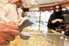 Продавец пересчитывает деньги в ювелирном магазине в Эр-Рияде 11 марта 2013 года. Саудовская Аравия, чьи финансы пострадали от низких цен на нефть, обнародовала планы сократить рекордный дефицит бюджета и реформировать энергосубсидии и намеревается увеличить доходы от налогов и приватизации. REUTERS/Stringer