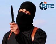 Боевик в маске и черной одежде с ножом, идентифицированный газетой Washington Post как британец Мохаммед Эмвази, размахивает ножом на видеозаписи, полученной Intel Group February 26 февраля 2015 года. REUTERS/SITE Intel Group/Handout via Reuters