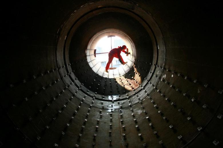 A worker checks steel pipes at an oil field preparing for oil and gas exploitation in Yilong, Sichuan province December 10, 2008. REUTERS/Stringer