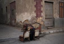 A woman sits on a chair in an alley inside the cemetery area where she lives east of Cairo, Egypt, September 6, 2015. . REUTERS/Asmaa Waguih