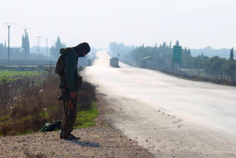 A fighter from a coalition of rebel groups called ''Jaish al Fateh'', also known as ''Army of Fatah'' (Conquest Army), secures a road as he waits for the passage of a convoy evacuating fighters and civilians from the two besieged Shi'ite towns of al-Foua and Kefraya in the mainly rebel-held northwestern province of Idlib, Syria December 28, 2015.  REUTERS/Ammar Abdullah