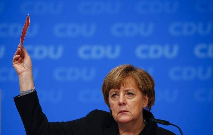German Chancellor and leader of the Christian Democratic Union (CDU) Angela Merkel holds up her voting card during a vote on a resolution about refugees at the CDU party congress in Karlsruhe, Germany December 14, 2015. REUTERS/Kai Pfaffenbach