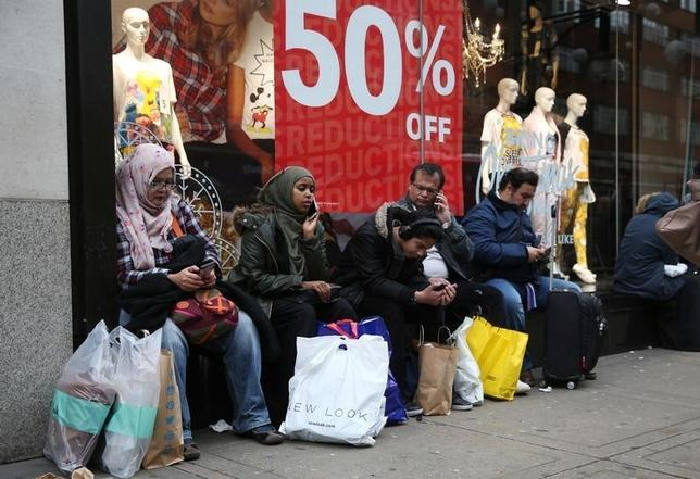 Shoppers rest with their purchases outside of a store on Oxford Street in London, Britain December 26, 2015.  REUTERS/Neil Hall   - RTX203CL