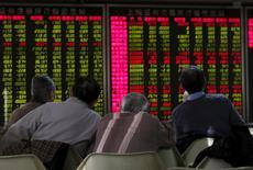 Hombres miran un tablero electrónico que muestra la información de las acciones, en una correduría en Pekín, China, 5 de enero de 2016. La campaña de seis meses de China por calmar a los mercados bursátiles enfrentará una prueba el martes, un día después de que una ola liquidadora motivó una suspensión de operaciones sin precedentes y puso en riesgo los esfuerzos de rescate del Estado que se estima han costado cerca de 140.000 millones de dólares. REUTERS/Kim Kyung-Hoon