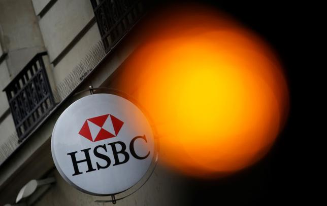 A traffic light shines orange near the HSBC bank logo, pictured at the bank buidling in Paris, June 15, 2015. REUTERS/Christian Hartmann