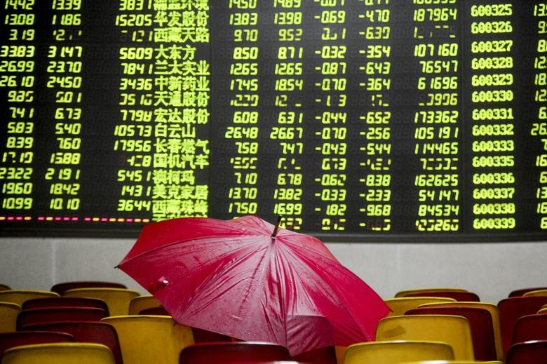 A red umbrella is placed on seats in front of an electronic board showing stock information, filled with green figures indicating falling prices, at a brokerage house in Dongguan, Guangdong province, China, January 5, 2016. REUTERS/Stringer