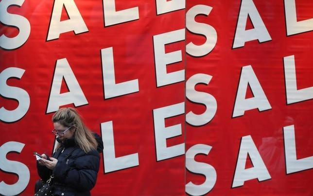 A woman checks her phone as she stands next to a store window advertising a sale on Oxford Street in London, Britain December 26, 2015.  REUTERS/Neil Hall