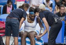 Serena Williams of the U.S. speaks to medical staff before withdrawing from the women's match between the U.S. and an Australian team at the Hopman Cup in Perth, Australia, January 5, 2016.  REUTERS/Tony McDonough/AAP