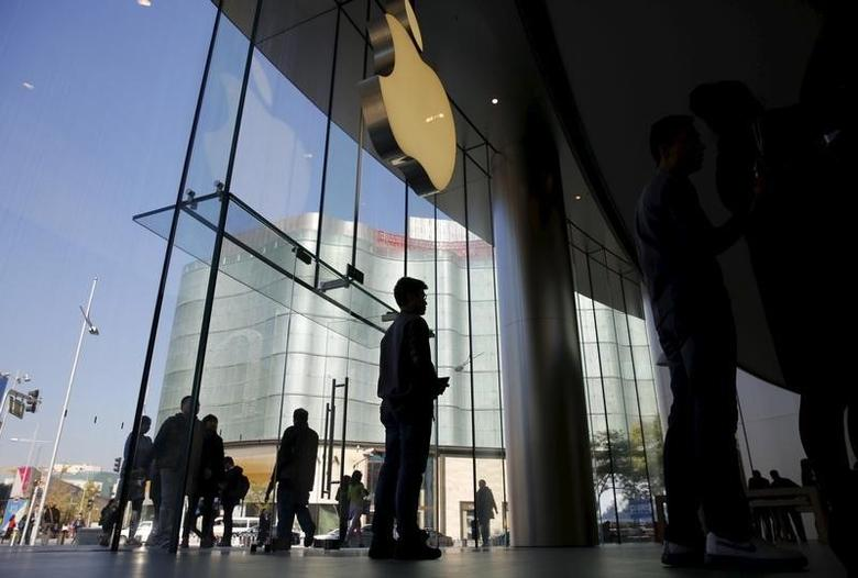 A staff member stands beneath Apple's logo at an apple store in Beijing, November 2, 2015. REUTERS/Kim Kyung-Hoon