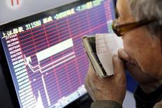 El Ibex-35 suavizó el jueves al cierre las pérdidas después de que la decisión de las autoridades chinas de suspender el mecanismo de interrupción de operaciones de bolsa permitiera recobrar parte de la confianza de los inversores. En la imagen, un inversor mira una pantalla de información bursátil en Shanghái, el 7 de enero de 2016. REUTERS/China Daily
