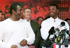 Ken Griffey Jr. (R) laughs with his father Ken Griffey Sr. (L) as they answer questions from the media in February 2000