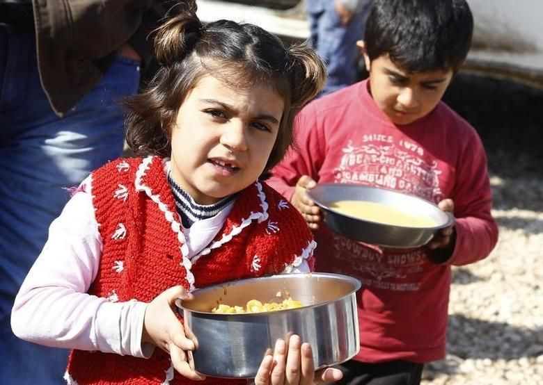 Kurdish refugee children from the Syrian town of Kobani carry food at a refugee camp in the border town of Suruc, Sanliurfa province February 1, 2015. REUTERS/Umit Bektas