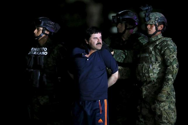 Joaquin ''El Chapo'' Guzman is escorted by soldiers during a presentation at the hangar belonging to the office of the Attorney General in Mexico City, Mexico January 8, 2016.  REUTERS/Edgard Garrido