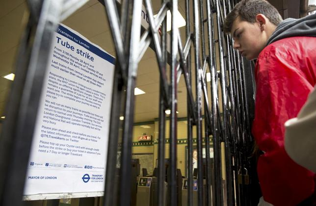 A tourist reads a notice posted at the closed gates of an underground station during the tube strike in London, in this file photograph dated April 29, 2014.  REUTERS/Neil Hall/files