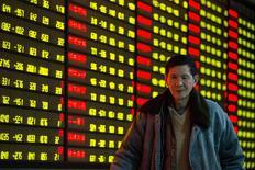 Investidor passa por painel com informações de ações em corretora de Nanjing, na China. 11/01/2016 REUTERS/China Daily
