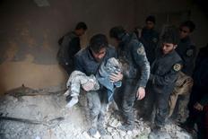 Мужчина несет ребенка, выжившего под обломками строения на месте, которое, по словам активистов, стало объектом удара российской авиации в городе Дума к востоку от Дамаска 10 января 2016. По меньшей мере 12 детей погибли в понедельник в результате удара, предположительно, российской авиации, по школе в Сирии в захваченном повстанцами городе провинции Алеппо, сообщила правозащитная организация Syrian Observatory for Human Rights. REUTERS/Bassam Khabieh