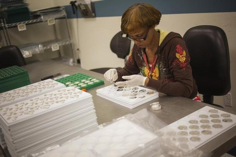 A quality control agent examines 2013 enhanced silver eagle silver coins at the United States West Point Mint facility in West Point, New York June 5, 2013.  REUTERS/Shannon Stapleton