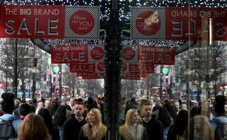 Shoppers are reflected in a store window as they pass sales advertisements on Oxford Street in London, Britain December 26, 2015.   REUTERS/Neil Hall