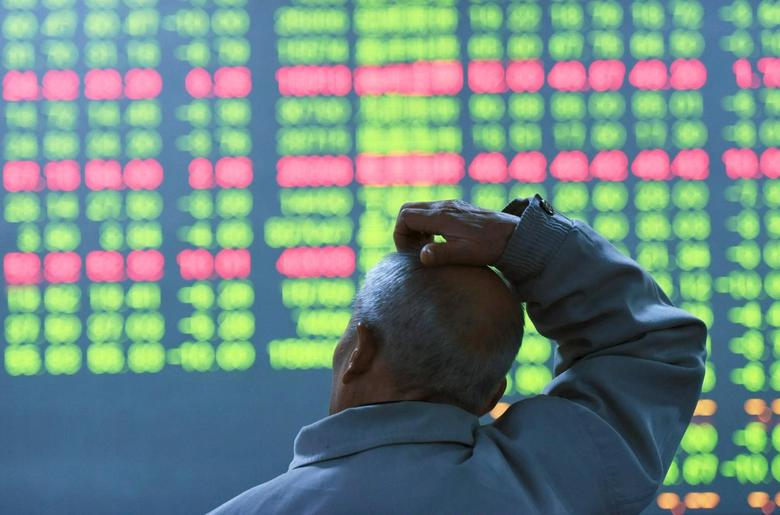 An investor looks at an electronic screen showing stock information at brokerage house in Hangzhou, Zhejiang Province, China, January 11, 2016. REUTERS/China Daily