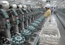 La economía de China probablemente creció cerca de un 7 por ciento en 2015 y sumó 13 millones de nuevos empleos, dijo el martes la principal agencia de planificación económica al anunciar la aprobación de grandes proyectos de infraestructura para evitar los riesgos de una mayor desaceleración. En la imagen, un trabajador en una planta de algodón en Youngor, Aksu, región autónoma de Xinjiang, el 1 de diciembre de 2015.   REUTERS/Dominique Patton