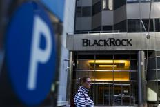 A woman walks next to a BlackRock sign pictured in the Manhattan borough of New York, October 11, 2015.  REUTERS/Eduardo Munoz