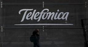 A reflection of a man talking on his phone is seen outside Telefonica's flagship store in central Madrid, Spain, April 28, 2015.  REUTERS/Sergio Perez