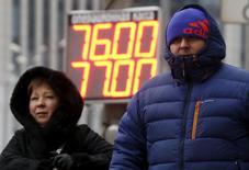 Люди проходят мимо таблички с курсами обмена валюты в Москве 12 января 2016 года. Глава департамента денежно-кредитной политики Банка России Игорь Дмитриев сказал, что регулятору пока нет необходимости пересматривать рисковый сценарий, предусматривающий цену на нефть на уровне $35 за баррель, но вероятность его реализации в текущих условиях выросла. REUTERS/Sergei Karpukhin