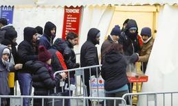 Alemania registró un superávit presupuestario mayor al esperado de 12.100 millones de euros en 2015 y utilizará esos recursos para financiar los costes adicionales por recibir e integrar a refugiados, dijo el miércoles el ministro de Finanzas Wolfgang Schäuble. En la imagen, un grupo de emigrantes hace cola para entrar en una tiendaen la Oficina de Salud y Asuntos Sociales de Berlín, el 5 de enero de 2016. REUTERS/Hannibal Hanschke