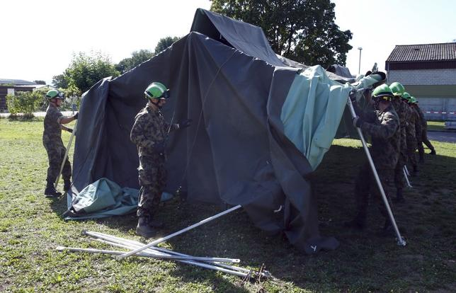 Swiss Army personnel build a tent outside a refugee camp in Lyss, Switzerland, September 2, 2015. REUTERS/Ruben Sprich