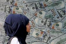 Женщина проходит мимо рекламной афиши пункта обмена валюты в Каире. 19 ноября 2015 года. Доллар снизился в ходе торгов на азиатских рынках в пятницу, растеряв достижения начала дня, поскольку фьючерсы на нефть резко упали, а динамика китайских акций отбила аппетит инвесторов к риску.  REUTERS/Mohamed Abd El Ghany