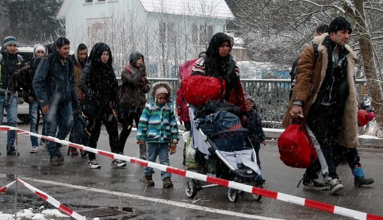 Migrants stay in queue during heavy snowfall before passing Austrian-German border in Wegscheid in Austria, near Passau November 22, 2015. REUTERS/Michael Dalder -