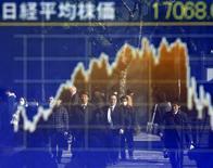Personas se reflejan en un tablero electrónico que muestra el índice Nikkei, afuera de una correduría en Tokio, Japón. 14 de enero de 2016. Las acciones japonesas bajaron el viernes tras una sesión volátil, devolviendo sus ganancias iniciales una vez que los precios del petróleo descendieron y después de que el responsable del Banco de Japón dijo que no tenía planes inmediatos para seguir aliviando la política monetaria. REUTERS/Toru Hanai