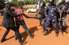 A supporter of Uganda's former Prime Minister Amama Mbabazi wrestles with the gun of a policeman, as riot police disperse a gathering in Jinja town in eastern Uganda September 10, 2015.  REUTERS/James Akena