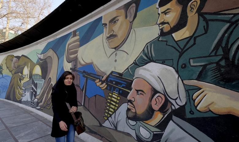 An Iranian woman walks past a revolutionary mural in Tehran, Iran, January 17, 2016. REUTERS/Raheb Homavandi/TIMA