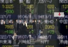 Personas se reflejan en un tablero electrónico que muestra información bursátil, afuera de una correduría en Tokio, Japón. 14 de enero de 2016. Las mayoría de las bolsas de Asia subía el martes luego de que las acciones de Shanghái repuntaron por unos datos que revelaron un crecimiento económico ralentizado en China, lo que avivó las esperanzas de que Pekín ofrezca un estímulo. REUTERS/Toru Hanai