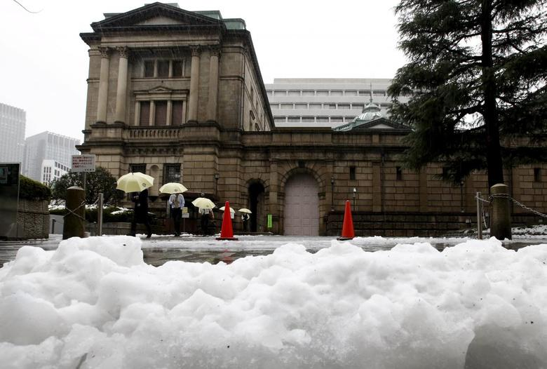 People holding umbrellas walk in front of the Bank of Japan building after snowfall in Tokyo, Japan January 18, 2016. REUTERS/Toru Hanai