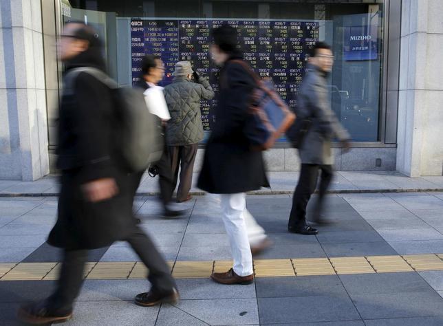 1月20日、甘利明経済再生相は、月例経済報告等に関する関係閣僚会議後に会見し、市場の動揺は「リスクオンとリスクオフの切り返し」との見方を示した。写真は株価ボードの前を通過する人々、都内で撮影(2016年 ロイター/Toru Hanai)