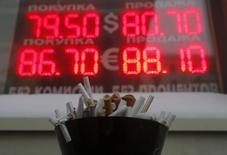 Полная окурков пепельница напротив табло с котировками валют в Москве 20 января 2015 года. Рубль существенно подешевел на торгах среды до исторических минимумов, пробив отметку 81 за доллар, на фоне снижения нефтяных цен на многолетние минимумы из-за переизбытка предложения на нефтяном рынке. REUTERS/Maxim Shemetov