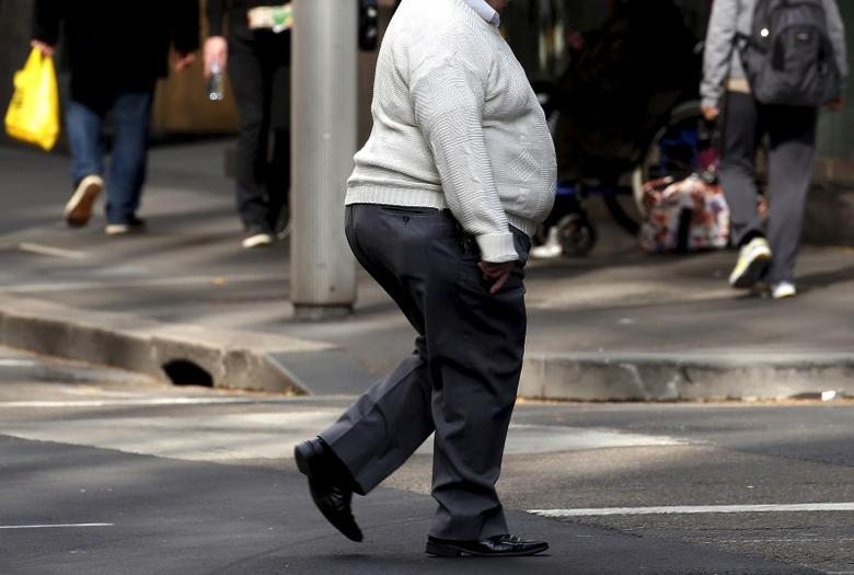 A man crosses a main road as pedestrians carrying food walk along the footpath in central Sydney, Australia, August 12, 2015. REUTERS/David Gray
