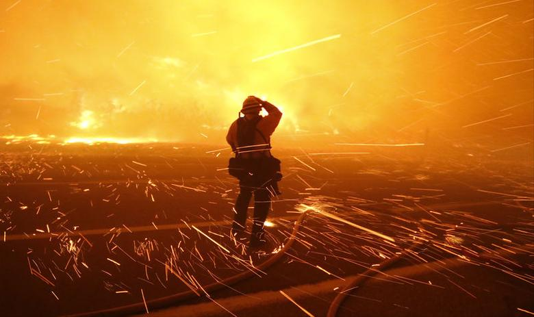 Fire photographer Tod Sudmeier gets hit with flying embers from strong winds at the Solimar brush fire that started early Saturday morning in Ventura County, California December 26, 2015. REUTERS/Gene Blevins