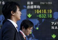 Unos hombres caminan junto a un tablero electrónico que muestra el índice Nikkei, afuera de una correduría en Tokio, Japón. 20 de enero de 2016. Las bolsas de Asia y el dólar cedían sus ganancias el jueves luego de que los volátiles precios del crudo no lograron mantener un rebote y oscilaron a la baja. REUTERS/Toru Hanai
